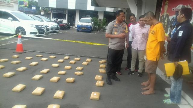 Kapolres Depok, Didik Sugiarto dengan latar belakang bungkusan ganja kering yang berhasil diamankan.